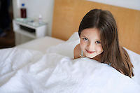Little girl sitting up in bed portrait