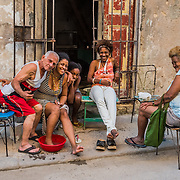 A group of women and an older gentleman share a laugh outside their front door during a pedicure in Havana.
