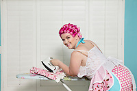 Portrait of happy young woman ironing