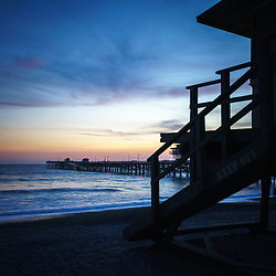 San Clemente lifeguard tower one and San Clemente pier sunset picture. San Clemente California is a coastal beach city along the Paciific Ocean in the Western United States of America. Photo is high resolution. Copyright ⓒ 2017 Paul Velgos with All Rights Reserved.