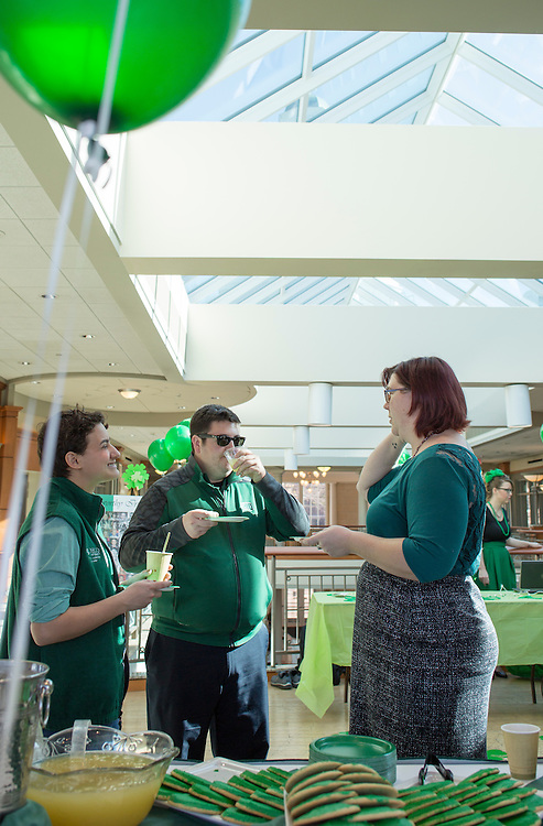 Claire Seid, left, a junior Multicultural Leadership Ambassador studying sociology, Thomas Raimondi, center, a coordinator in the Office of Diversity and Inclusion's Office of Multicultural Student Access and Retention, and Sarah Jenkins, right, the program coordinator for the Women's Center, talk to one another and enjoy refreshments at the Office of Diversity and Inclusion's St. Patrick's Day celebration on March 17, 2016.