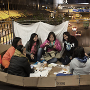 Filipino women sit and chat and share food on a walk way across a busy main road in Central on a Sunday, their weekly day off.  Hong Kong has a huge population of Filipinos, mostly woman who work as domestic workers in the business community. Most of the women have no private accomodation so on their days off Central Hong Kong is heaving with women who meet in puclic to socialize. <br />