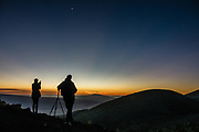 Silhouetted people on Mauna Kea's Sunset Hill admire the crescent moon and rays of twilight fading from orange to dark blue behind Hualalai volcano. Hualalai (8271 feet elevation) is the westernmost and third-youngest of the five shield volcanoes that form the Big Island of Hawaii. Hualalai rose above sea level about 300,000 years ago. Last erupted in 1801, Hualalai is still active and may erupt again within the next century, which will be a rude shock to the town of Kailua-Kona built on its flanks. For colorful sunset views of the Saddle Road region, walk 1 mile round trip (160 ft gain) to the cinder cone of Pu'u Kalepeamoa, or Sunset Hill, from the Onizuka Center for International Astronomy Mauna Kea Visitor Information Station at 9200 ft elevation. About a million years old and last erupted 6000 to 4000 years ago, Mauna Kea is a dormant volcano on the Big Island of Hawaii, USA. Mauna Kea stands 13,800 feet above sea level and is the highest point in the state of Hawaii. Measured from its base on the ocean floor, it rises over 33,000 ft, significantly greater than the elevation of Mount Everest above sea level. Paving ends at the Visitor Info Station, and four-wheel drive is recommended to reach the top, where Mauna Kea summit's dry, clear, stable air makes one of the world's best sites for astronomy.