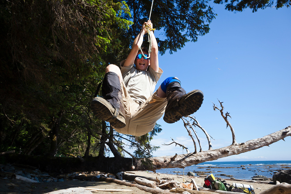 Zach Podell-Eberhardt leaps into the air hanging from a rope swing found on the beach along the West Coast Trail, British Columbia, Canada.