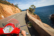 Motor scooter driver point of view while driving a coast road near Cannes, France, the French Riviera. Road is along the Meditteranean coast.