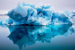 A blue iceberg reflected in the Arctic Ocean, Svalbard, Norway