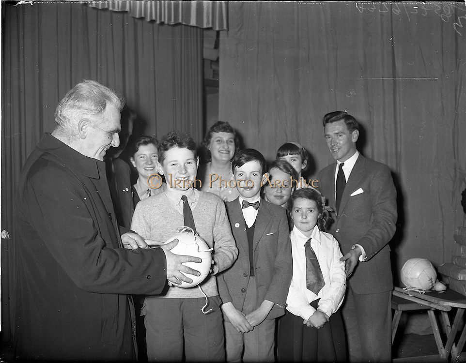 20/03/1959<br /> 03/20/1959<br /> 20 March 1959<br /> Gael Linn singing competition and concert at Dungannon, Co. Tyrone.<br /> Very Rev. Dean Quinn, P.P., Dungannon (left) presenting presenting 2nd prize winner Seamus Mac Mathuna with a football in St. Patrick's Hall, Dungannon. Other prize winners included are, Margaret Dynes, Ann Lawless, Ann Corey, Cormac Hamill, George Mc Mahon and Nora Lappin, Gael-Linn National Organiser, Diarmuid O'Broin is on right.