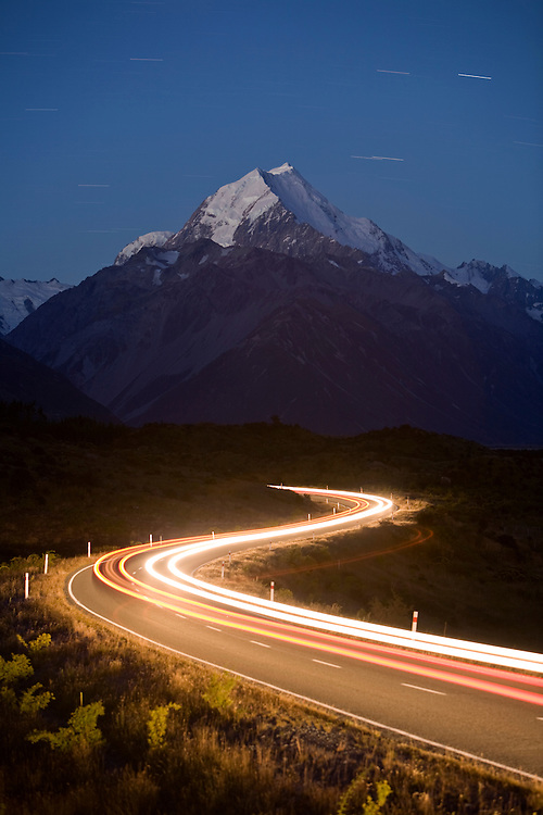 New Zealand, South Island, Aoraki Mount Cook National Park, Car headlights driving on two-lane highway under glacier-covered summit of Mount Cook at nightfall on summer evening
