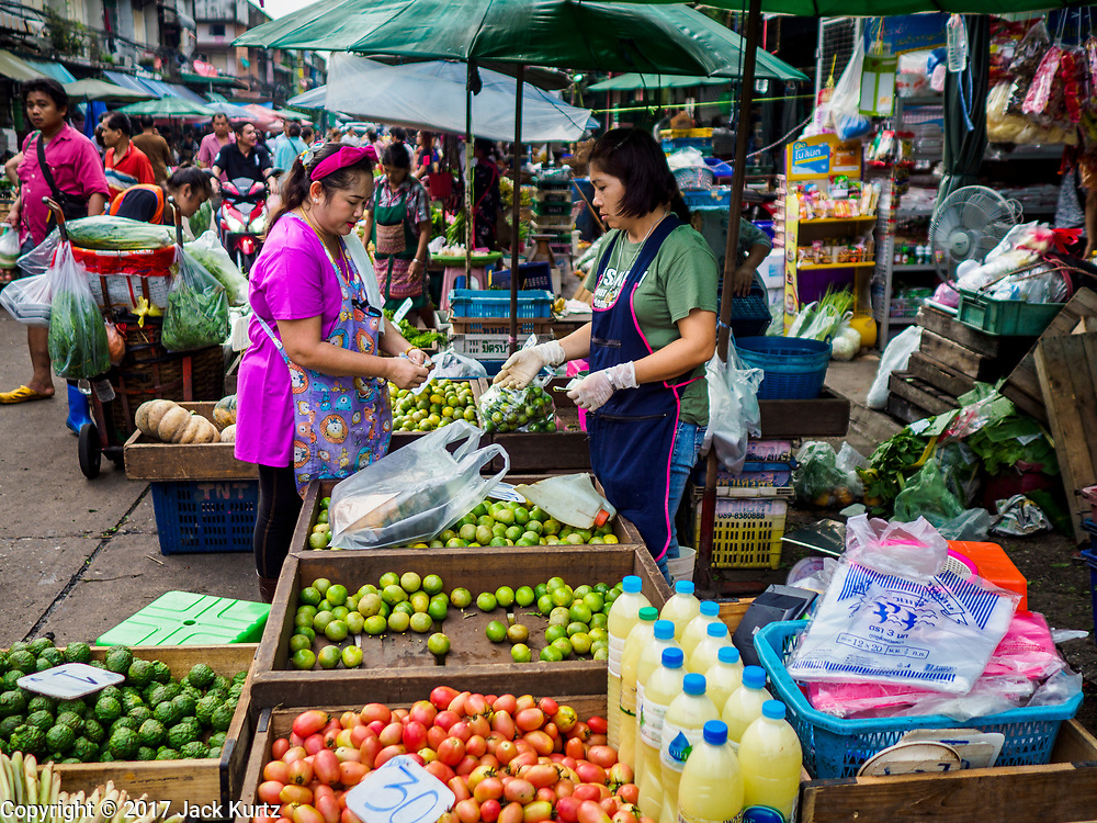 08 JUNE 2017 - BANGKOK, THAILAND: A vendor selling chilies and fresh vegetables in Khlong Toey Market, Bangkok's main fresh market. Thai consumer confidence dropped for the first time in six months in May following a pair of bombings in Bangkok, low commodity prices paid to farmers and a sharp rise in the value of the Thai Baht versus the US Dollar and the EU Euro. The Baht is surging because of political uncertainty, related to Donald Trump, in the US and Europe. The Baht's rise is being blamed for a drop in Thai exports. This week the Baht has been trading at around 33.90 Baht to $1US, it's highest point in two years.      PHOTO BY JACK KURTZ