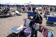 Roma 8 Agosto 2007.Un immigrato venditore ambulante vende oggetti sulla spiaggia di Ostia..An immigrant vendor, selling souvenirs walk in Ostia beach.