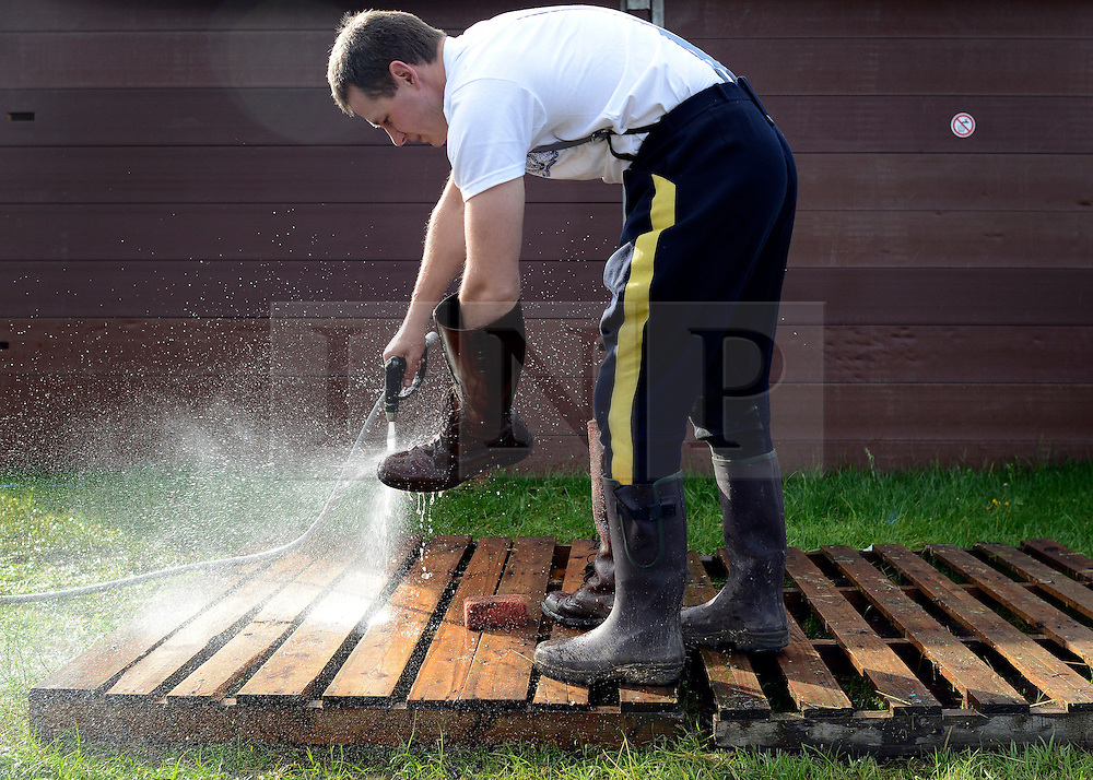 © Licensed to London News Pictures. 11/05/2012. Windsor, UK A Royal Canadian Mounted Police officer washes mud off his boots using a hosepipe drawn off the River Thames.  The Royal Windsor Horse Show in Windsor, England on May 11 2012. Photo credit : Stephen Simpson/LNP