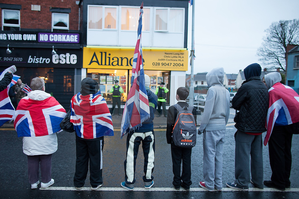 """© Licensed to London News Pictures . 11/01/2013 . Belfast , UK . Loyalist protesters stand in the middle of the road opposite the office of the Alliance Party on the Newtownards Road in East Belfast today (11th January 2013) ahead of """" Operation Standstill """" . The protest is one of many that have been held since Belfast City Council voted to stop flying the Union flag above Belfast City Hall . Photo credit : Joel Goodman/LNP."""