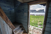 View of the National Geographic Explorer from an old abandoned wooden house in the village of Måstad, Lofoten archipelago, Norway.