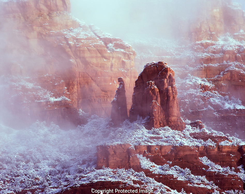 Capitol Butte with The Watcher rock tower formation in snow and fog during morning light Sedona AZ