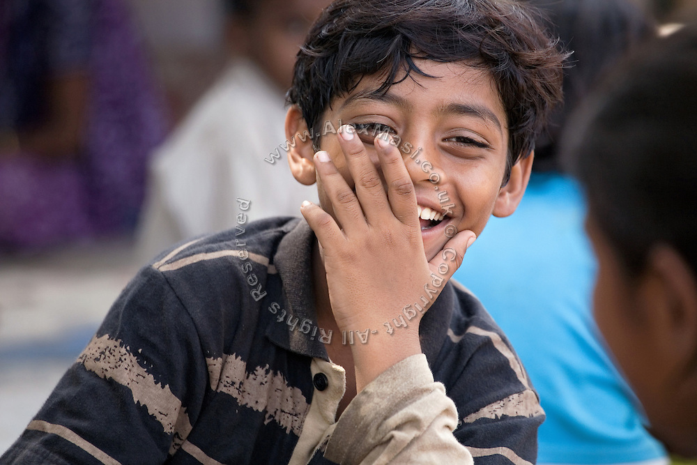 Azharuddin Ismail, 10, the child actor playing the role of 'young Salim', the brother of Jamal, protagonist of Slumdog Millionaire, the famous movie winner of 8 Oscar Academy Awards in December 2008, is laughing with friends in the slum where he still lives with his family next to the train station of Bandra (East), Mumbai, India. Various promises were made to lift the two young actors (Azharuddin Ismail and Rubina Ali) from poverty and slum-life but as of the end of May 2009 anything is yet to happen. Rubina's house was recently demolished with no notice as it lay on land owned by the Maharashtra train authorities and she is now permanently living with her uncle's family in a home a stone-throw away in the same slum. Azharuddin's home too was demolished in the past two weeks, as it happens every year in his case, because the concrete walls were preventing local authorities to clear a drain passing right behind it. As usual, his father is looking into restoring the walls as soon as the work on the drain has been completed.