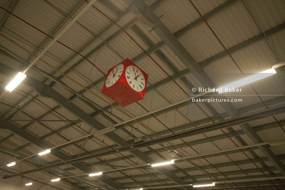 Red clock hangs from warehouse roof of cross-docking area of of Royal Mail's DIRFT logistics park in Daventry