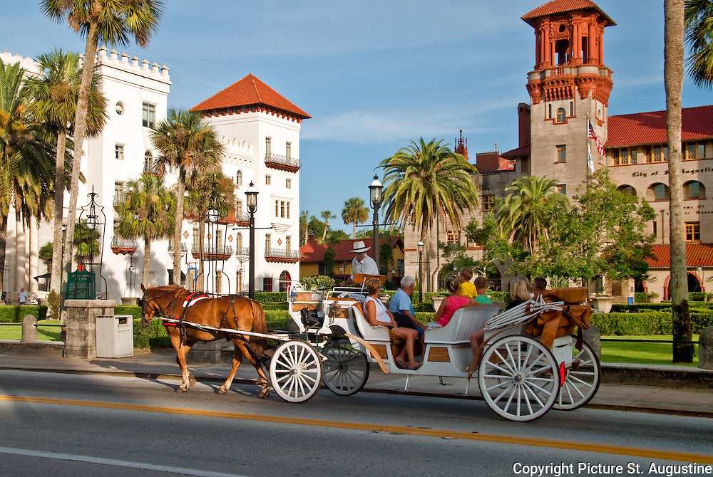 A horse and carriage passes the Lightner Museum/St. Augustine City Hall and the Casa Monica Hotel in historic St. Augustine, Florida