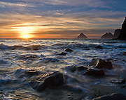"The sun sets over waves of the Pacific Ocean near winter solstice at Three Arch Rocks, Oceanside, Oregon, USA. Published in ""Light Travel: Photography on the Go"" by Tom Dempsey 2009, 2010."