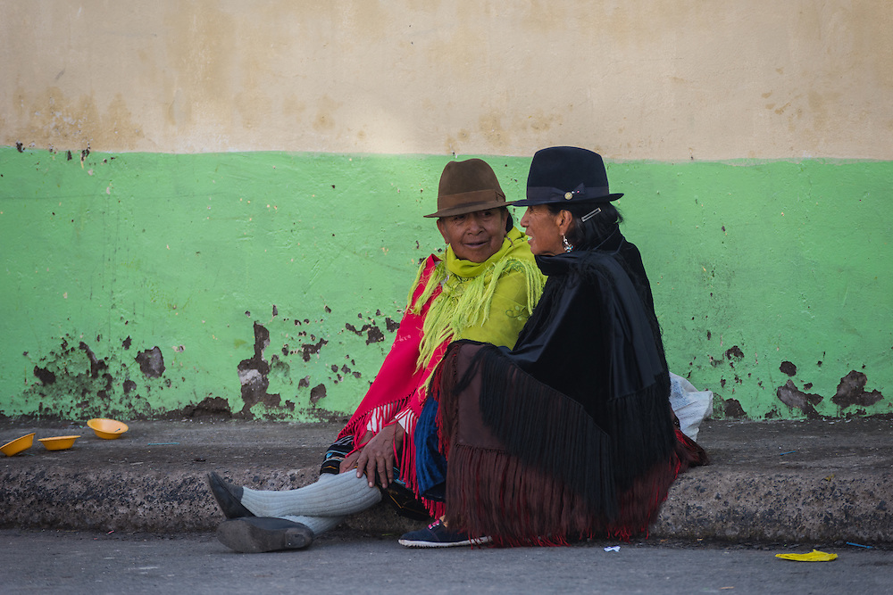 Two women sitting on the ground and chatting, Zumbahue, Ecuador.