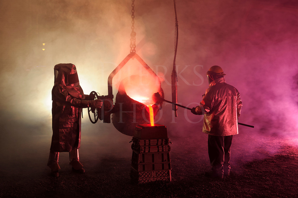 Pouring hot molten iron in a steel mill reenactment with steelworkers using small ladle bucket...hot, smoky, and dangerous, Bethlehem Steel, Pennsylvania, USA.