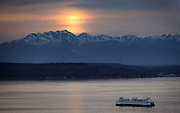 A ferry heads towards Bremerton, Bainbridge Island and the Olympic mountains in the background under clear skies. (Ellen M. Banner / The Seattle Times)