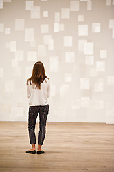 "Mira Schendel at Tate Modern in London. <br /> Tate Modern employee poses next to works entitled ""Variants 1977"" by Mira Schendel, Tate Modern, London, Tuesday, 24th September 2013. Picture by Piero Cruciatti / i-Images"