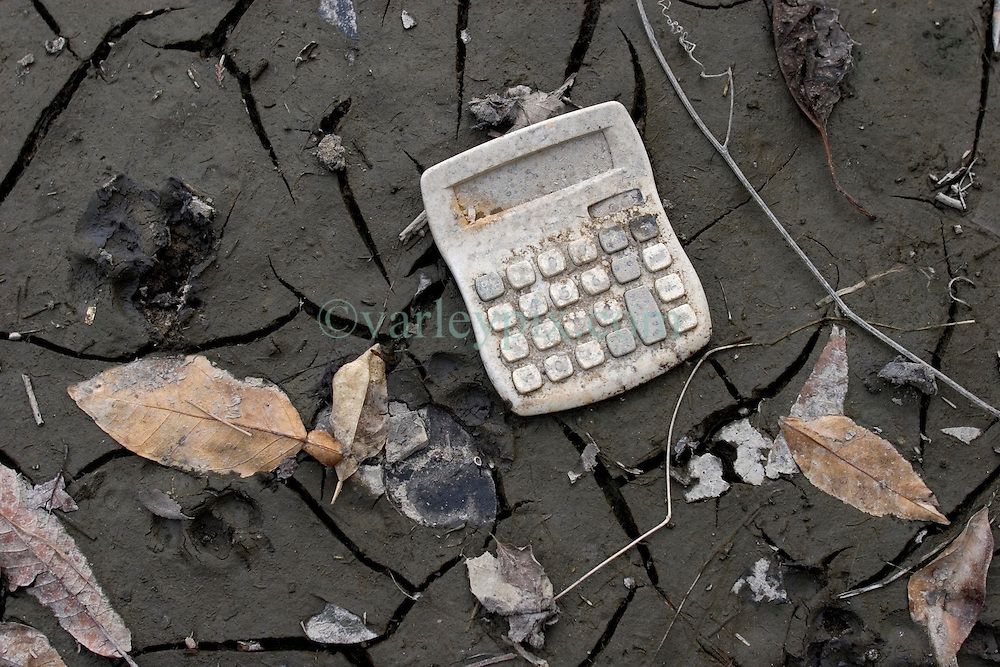 01 October, 05.  New Orleans, Louisiana. Lower 9th ward. Hurricane Katrina aftermath. <br /> The remnants of the lives of ordinary folks, now covered in mud as the flood waters recede. A calculator lies in the mud.<br /> Photo; ©Charlie Varley/varleypix.com