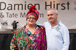 © Licensed to London News Pictures. 14/06/2012. LONDON, UK. Artist Damien Hirst (R) and Kids Company founder Camilla Batmanghelidjh (L) pose at an art workshop in Covent Garden, London, today (14/06/12). In celebration of Damien Hirst's current exhibition at the Tate Modern, the artist held a pubic art event giving British School children the chance to create their own versions of his iconic spin paintings. Photo credit: Matt Cetti-Roberts/LNP