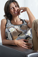 Pregnant woman sitting in armchair indoors