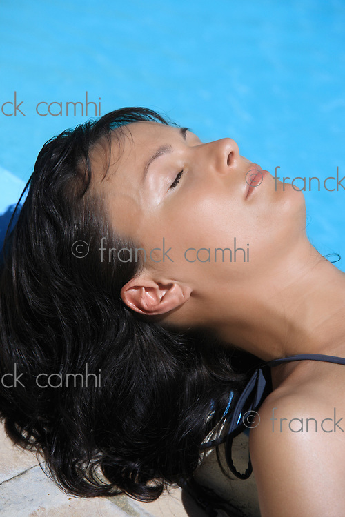 young beautiful caucasian brunette woman relaxing or sleeping near a swimming pool getting tanned by the sun