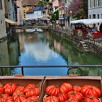 Coeur de Boeuf tomatoes and Thiou Canal in Annecy, France <br /> If you ask where Annecy&rsquo;s three-day-a-week framers&rsquo; market is held, the quick answer will be along Rue Sainte Claire.  But several vendors also raise their tents, stalls or rickety tables along the bridges crossing the Thiou Canal and then line them with fresh produce, fruits and flowers.  It is hard to decide which view is more beautiful: the bright red Coeur de Boeuf tomatoes or the waterway in the background.