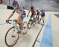 Coach Carlos Lavorde, right, teaches Carlos Rocha, 17, before he starts his training session next to Daniel Jimenez, 17, center, and Max Thilen, 13, at the Bryan Piccolo park's velodrome on Monday June 29, 2009. Staff photo/Cristobal Herrera.