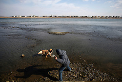 A Chinese man throws a rock for his dog to catch along the river bank of the Yalu River where across is the North Korean bank of the Yalu River near the town of Sinuiji across the Chinese city of Dandong, Liaoning Province, China on 06 April 2013. North Korean leader Kim Jong-un has ordered the country's military to increase artillery production, a televised report out of Pyongyang showed 06 April.