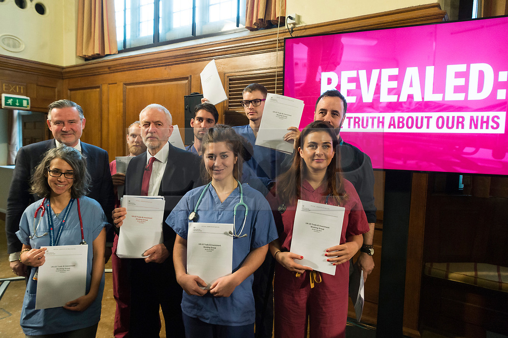 """© Licensed to London News Pictures. 27/11/2019. London, UK. British Labour party leader Jeremy Corbyn and NHS workers hold revealing official government documents showing the US is demanding that the NHS will be """"on the table"""" in talks on a post-Brexit trade deal on the National Health Service. Photo credit: Ray Tang/LNP"""