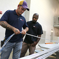 Paul Landry and Robert Williams, installers with City Tele Coin in Bossier City, Louisiana, work on running communications cables through conduit for new monitor systems that are being installed inside the A Pod cell and throughout the Lee County Jail on Tuesday.