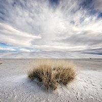White desert sand dunes under a blue sky with white clouds in America