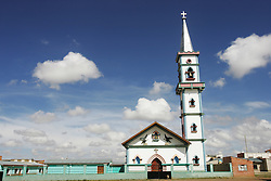 "Portrait of a church that Father Sebastian Obermaier built in El Alto, Bolivia. a town he has lived in for 27 years .  ""I don't feel Bolivian, I feel Aymara"" he says, referring to the Aymara indigenous population that makes up more than 80% of El Alto. Father Obermaier has been designing and building churches in El Alto for the past 10 years, with a goal of building one church for every 10,000 inhabitants of the city, which currently has nearly 700,000 people living in it.  Everyone that visits Bolivia can see his numerous churches from the window of their airplane as it lands in El Alto.  The churches are marked by a style unique to Father Obermaier, that mixes indigenous symbols with tall towers and bright colors, that leave every church looking different, as if they were straight out of a children's pop-up book."