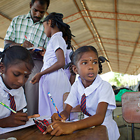 M. Dilushana, age 9 (looking up) in class in a UNICEF-supplied Temporary Learning Space.<br /> <br /> Sisters M. Dhanushika, age 11 and M. Dilushika, age 9 are from Sri Lanka's Tamil community. They lost their mother in 2006 after she was raped and killed, allegedly by TMVP troops loyal to Colonel Karuna. Their father has subsequently remarried and refuses to be involved in the upbringing of his daughters who live together in a temporary makeshift shelter supplied by UNHCR. The two sisters rely on their aunt and uncle for care. Dhanushika and Dilushika attend Vadamunai Government Tamil Mixed School but often miss classes because they must work collecting reeds which provides them their only source of income. Despite the challenges of their situation, Dhanushika is a particularly conscientious child. As well as taking responsibility for her own necessities, she is committed to her sister's well being. The girls rely on a meal provided by the school every day. Despite the support of neighbours, their present situation is not sustainable and they are likely to be admitted to the care of an orphanage in the near future. <br /> <br /> When fighting between the LTTE and Colombo Government forced the displacement of the local Tamil community in 2007, the Vadamunai Government Tamil Mixed School in Batticaloa District was closed. Since reopening in January 2009, the school has six teaching staff for 88 pupils from Grades 1-9. Before closure,136 pupils studied at the school. Poor road-infrastructure and the remote location of the school means that many staff have to commute for more than three hours. Five classes are held in a UNICEF-supplied Temporary Learning Space. Four other classes are conducted outside, beneath trees. Many of the students suffer with the trauma and stress associated with those living in conflict situations. The staff must deal with these issues as well as the personal difficulties that they themselves suffer living in a conflict environment. To further antagonise an already di