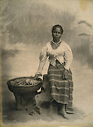 Woman in cloth and jacket with a basket and vegetables.<br /> Photograph by Skeen.
