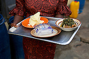 Joy carrying a tray of food at her restaurant.<br /> <br /> Joy Kalu runs Goodness Catering Services, which is a restaurant and events catering business.<br /> <br /> Joy began her catering business in 1999. She started off just making 10 or 15 soups to sell each day but soon the business grew and she started diversifying the range of food she sold. After three years she moved into her premises at the local market and her business developed into catering for events such as weddings and funerals.<br /> <br /> The main thing Joy learnt on the Youth for Technology training was the importance of capital investment.