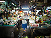 02 SEPTEMBER 2015 - BANGKOK, THAILAND: A woman walks through Bang Chak Market. The Bang Chak Market serves the community around Sois 91-97 on Sukhumvit Road in the Bangkok suburbs. About half of the market has been torn down, vendors in the remaining part of the market said they expect to be evicted by the end of the year. The old market, and many of the small working class shophouses and apartments near the market are being being torn down. People who live in the area said condominiums are being built on the land.         PHOTO BY JACK KURTZ