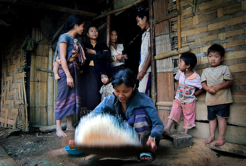 A woman in a mountain village near Luang Prabang, Laos, winnowing rice for her family.