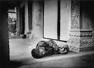 Young boy sleeps on pavement in front of tourist shops and cafes in Siem Reap, Cambodia.  The tourism district of Siem Reap is inhabited by children roaming and seaching for food scraps and loose change.