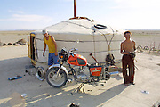 GOBI DESERT, MONGOLIA..08/31/2001.Boys repairing motorbike at their ger near Bayangovi..(Photo by Heimo Aga).