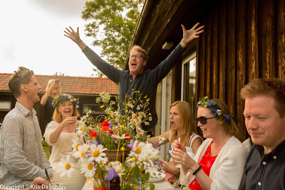 Man leading the singing of a Swedish folk song during the evening Midsummer meal on Öland, a Swedish island in the Baltic Sea. The longest day of the year is a beloved holiday in Sweden; the cities are empty as the locals take to the countryside for a day of dancing and singing with family and friends.