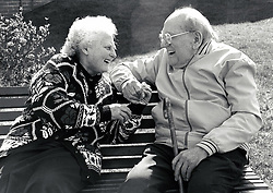 Elderly couple laughing on bench, Nottingham UK 1991