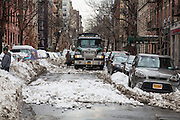 A large black Mack hauling truck driving through the snow on 34 West 13st Street New York City,  New York, United States of America, after the snowstorm in January 2016.  There are cars parked on both sides of the street buried in snow. The snowstorm brought more than 2 feet of snow in many areas, which broke many records.  (photo by Andrew Aitchison / In pictures via Getty Images)