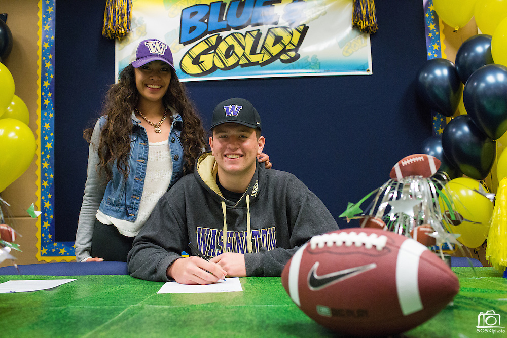 Jason Scempos and his girlfriend pose with a duplicate National Letter of Intent to play football at the University of Washington during the NCAA National Signing Day event at Milpitas High School in Milpitas, California, on February 4, 2015. (Stan Olszewski/SOSKIphoto)