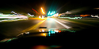 Car driving down a road at night, with the lights blurring past.