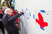 Charleston Mayor Joe Riley paints a dove on the wall during the inauguration of the Charleston Strong mural October 21, 2015 in Charleston, South Carolina. The wall is to commemorate the mass shooting at the historic Mother Emanuel African Methodist Episcopal Church last June.